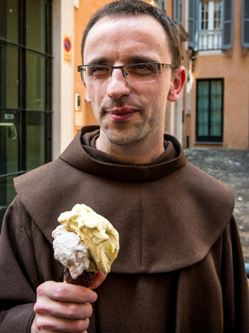 A priest enjoying a cone from gelateria Caffe Giolitti ice cream parlor, Rome