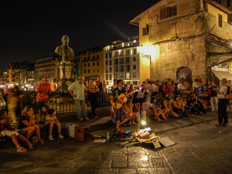 A busker entertains the evening crowds on the tiny piazetta in the middle of the Ponte Vecchio, Florence. (Photo by Joseph Maestri)